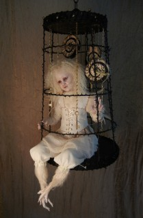 taxidermy artdoll assemblage of a white thornbird doll with feathered feet sitting in a suspended cage surrounded by hand painted clocks