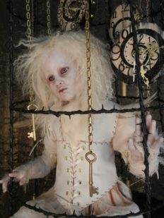 close-up of taxidermy artdoll assemblage of a white thornbird doll sitting in a suspended cage surrounded by hand painted clocks and hanging gold keys