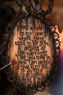 close-up of hand-painted poem on wooden board black lettering
