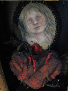 a close-up of mixed media assemblage impaled red heart in front of painted portrait of poet
