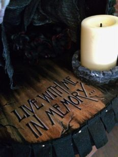 close-up of the hand painted base of altarbox with a battery powered candle