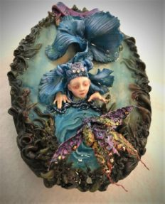 resin encased mixed media assemblage of a doll faced blue fish rising out of the water to see a bejeweled beetle.