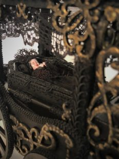 closeup deceased dollhouse doll in a funeral cart coffin