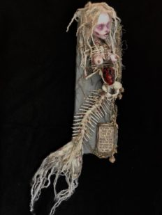 mixed media assemblage of a ghostly skeletal mermaid holding a bleeding heart goth doll repaint