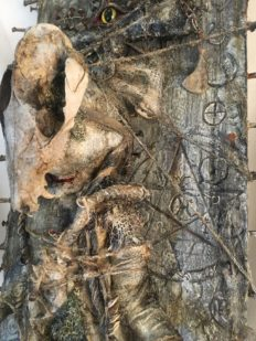 close up of mixed media taxidermy assemblage repainted babydoll decorated with bones mounted to witchy board occult artifact