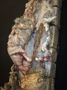 close-up of mixed media assemblage on board with severed, cracked and bleeding hands held up by chain and hanging from nails