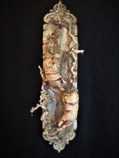 mixed media assemblage on board with severed, cracked and bleeding hands held up by chain and hanging from nails