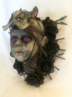 dark repainted baby doll head bone and flower headdress purple eyes