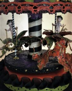 close-up of gothic striped carousel music box with tiny ghost skeletons riding bejeweled beetles black, orange, purple and green