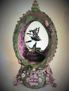 tiny gothic dancer wearing skull headdress and black tutu spins atop a bejeweled beetle in a velvety purple moss-covered egg music box