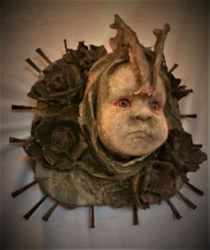 mixed media assemblage plaque repainted babydoll head with a jaw bone headdress and flowers and nails mounted on wood