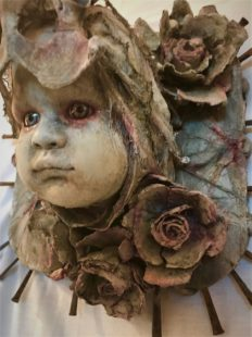 close-up of mixed media assemblage plaque repainted babydoll head with a bone headdress and flowers and nails mounted on wood
