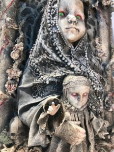 close up mixed media assemblage plaque repainted sainted robed baby doll holding a baby