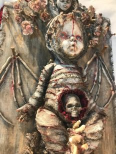 close-up of mixed media assemblage plaque bloody mummified babydoll with skeleton wings and a skull in the stomach