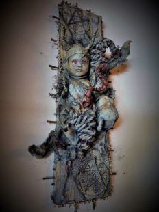 mixed media assemblage ghastly repainted baby dolls mounted on wooden board dark art pentagram