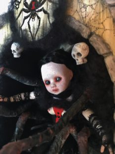 close-up shadowbox mixed media assemblage of a gothic black widow themed doll with 8 legs pale with black hair and red hour glass she is inside a carved box with hand-painted wooden signs
