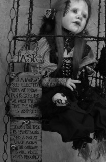 goth doll taxidermy assemblage sitting in a black cage surrounded by seven raven birds